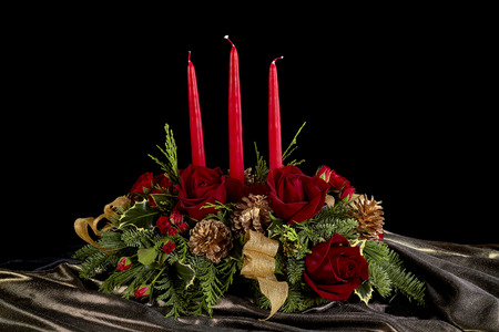 arreglo floral: Decorative flower arrangement with roses, red candles, gold pine cones and evergreen needles isolated on black