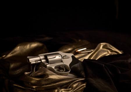 black velvet: Snubnose 38 revolver laying across gold satin and black velvet with 38 caliber bullets in the background