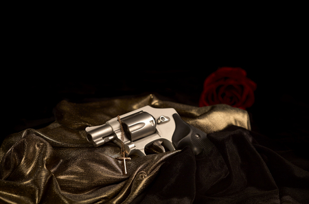 38: Snubnose 38 revolver laying across gold satin with a gold cross and black velvet an a red rose in the background with shallow depth of field Stock Photo