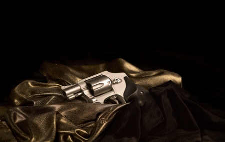 38 caliber: Snubnose 38 revolver laying across gold satin and black velvet