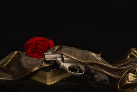 38 caliber: Snubnose revolver laying across gold bound book draped with Satin and a Red Rose Stock Photo
