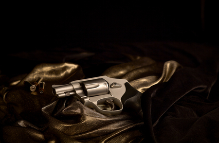 38 caliber: Snubnose 38 revolver laying across gold satin and black velvet with 38 caliber bullets in the background