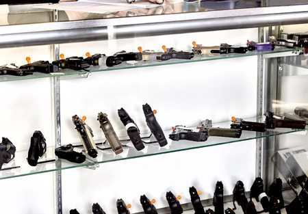 pistols: Rows of guns for sale in showcase of retail store with application on counter