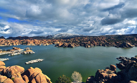 scrub cap: A lake surrounded by boulders and a snowcapped mountain with clouds and blue sky, located at Watson Lake, Prescott, Arizona