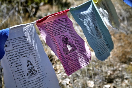 sutra: Buddhist prayer flags hanging from tree to tree blowing in the wind Stock Photo