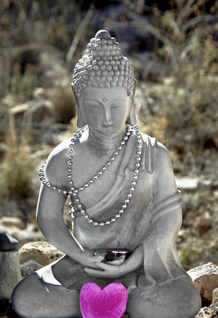 masters of rock: Cement statue of Buddha in lotus position with prayer beads and heart Stock Photo