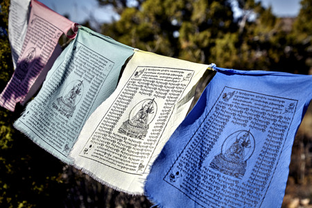 masters of rock: Buddhist prayer flags hanging from tree to tree blowing in the wind Stock Photo