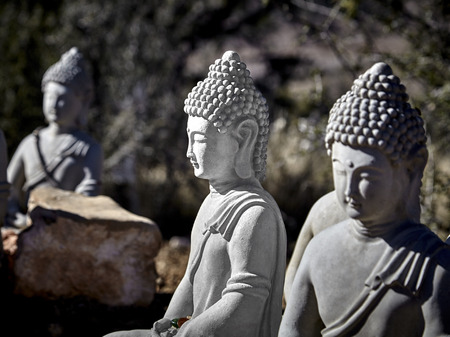 masters of rock: Buddhist figures made of cement sitting in meditation with prayer offerings