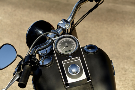 ignition: Black motorcycle speedometer with odometer, ignition switch, handlebars, headlight, and hand brakes