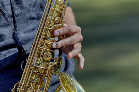muscian: Close up of the hands of a young adult man playing a saxophone