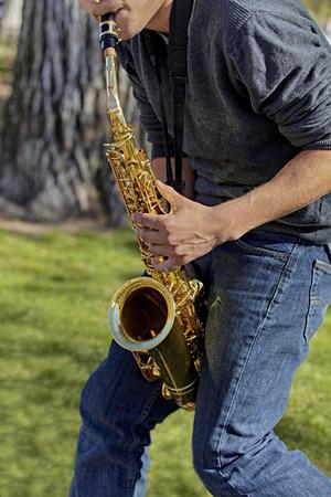 soprano saxophone: Hombre que toca el saxofón en un parque