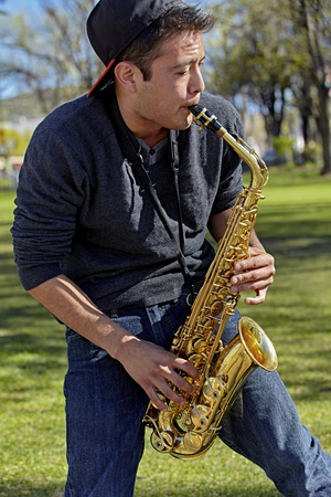 muscian: Young man playing a saxophone in the park Stock Photo