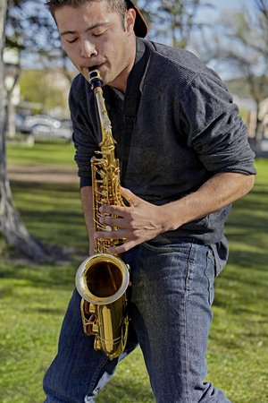muscian: Man playing the saxophone in a park