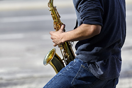 muscian: Young adult man playing a saxophone