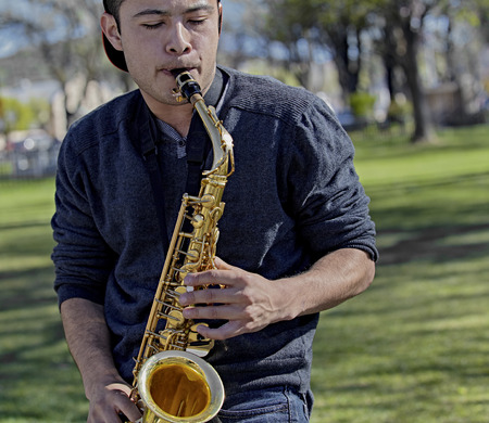 muscian: College Student playing the Saxophone in a Park