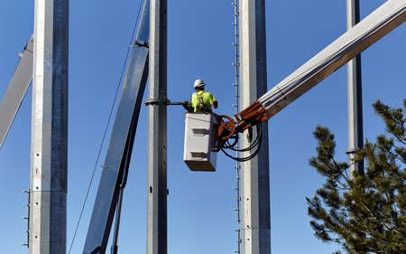 servicing: Utility worker in a boom crane basket servicing utility poles