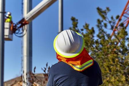 electricity company: Utility Line Supervisor monitoring the installation of utility poles