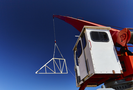 rafter: Crane that has suspended a roof truss in the air against blue sky