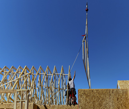 rafter: Construction workers reaching up to a roof trusses to install on a new home