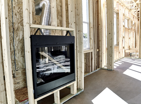 fireplace home: Framed home showing installation of a gas fireplace with vent