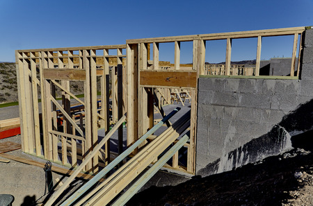 roof framing: Wood Framed home on side of hill under construction Stock Photo