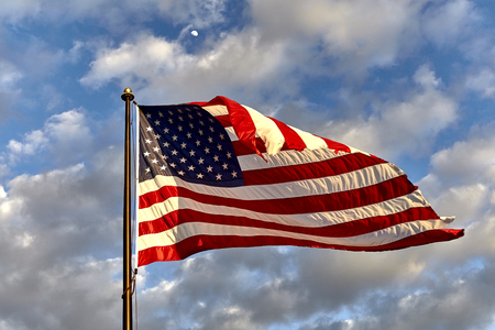 flagpole: American flag on flagpole waving in the wind against clouds, blue sky and the moon