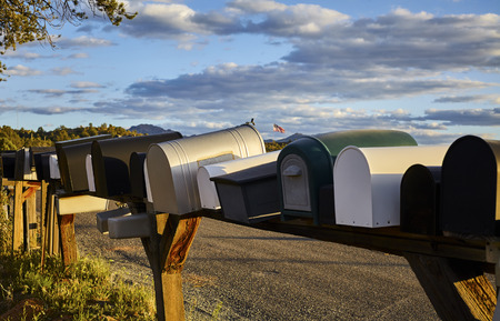united states postal service: Row of rural mailboxes with an American Flag in the distance
