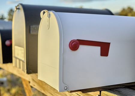 united states postal service: White Mailbox with a red flag in the down position with shallow depth of field
