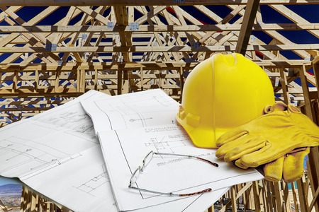 work gloves: A set of blueprints with hardhat, work gloves and reading glasses with wood framed structure in background Stock Photo
