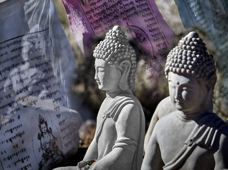 masters of rock: Buddhist figures made of cement sitting in meditation with prayer offerings and prayer flag