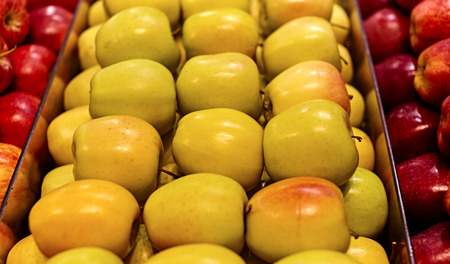 bushel: Bushel full of yellow apples in a row with red apples on the sides and shallow depth of field