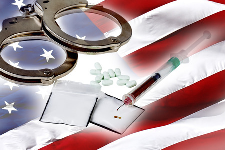 hypodermic needle: Heroin in a hypodermic needle  with packets of heroin powder and pills with an American Flag Stock Photo