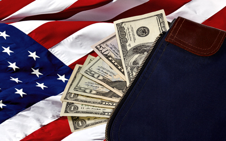 fifty dollar bill: Money bag containing US Currency including a hundred dollar bill, a fifty, two twenties and three ones on an American flag Stock Photo
