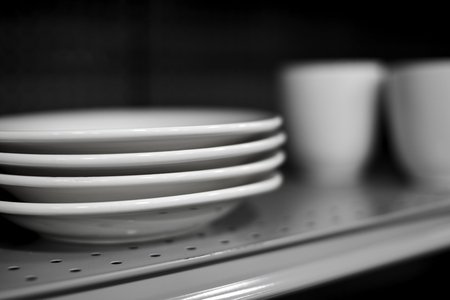 throw cushion: Four White Ceramic Dinner Plates on Shelf with white mugs in background with shallow depth of field Stock Photo