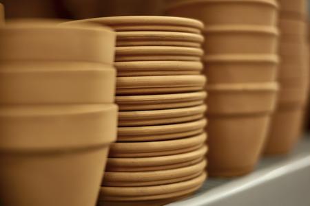 ollas de barro: Filas de los crisoles de arcilla con las bandejas en estante con poca profundidad de campo Foto de archivo