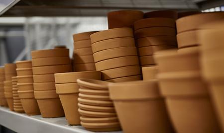 ollas de barro: Estantería llena de macetas de arcilla con poca profundidad de campo Foto de archivo