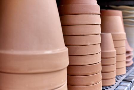 ollas de barro: Pila de crisoles de arcilla en un estante con poca profundidad de campo