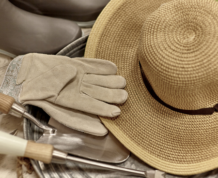 work boots: Garden work gloves, sun hat, rubber work boots and trowel on a tray with shallow depth of field