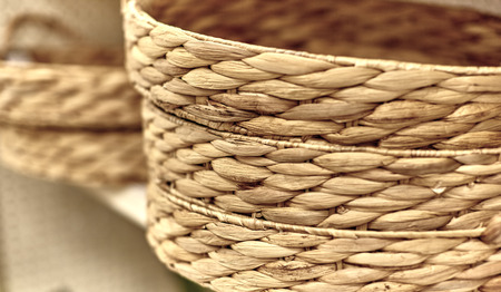 garment industry: Natural fiber storage baskets stacked on store shelf with shallow depth of field