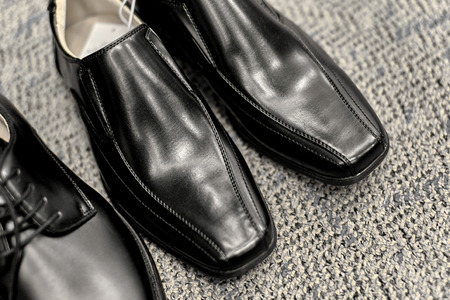 dress shoes: New mens black dress shoes on carpet with shallow depth of field