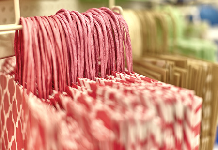 gift bags: Pink gift bags with close up of handles hanging on rack in retail store with shallow depth of field