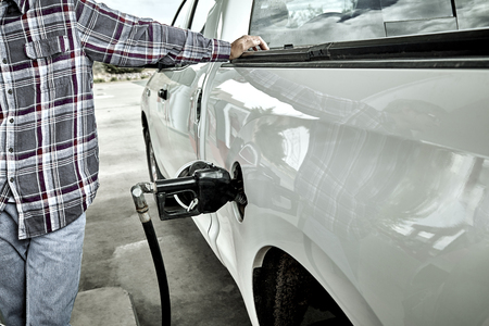 unleaded: Man standing next to pick up truck pumping gas Stock Photo