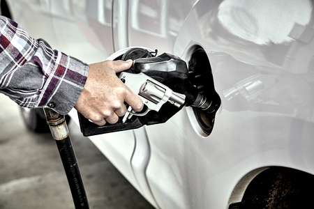 gas nozzle: Mans hand holding a Revolver and gas nozzle while  pumping gas into parked vehicle
