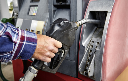unleaded: Mans hand removing gas nozzle from gas pump in preparation to refuel