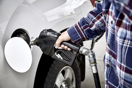 gas nozzle: Mans hand holding gas nozzle while  pumping gas into parked vehicle