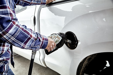 gas nozzle: Mans hand holding three one hundred dollar bills  and gas nozzle while  pumping gas into parked vehicle Stock Photo