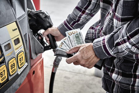 fueling pump: Mans hand holding three one hundred dollar bills and gas nozzle while preparing to pump gas into parked vehicle Stock Photo
