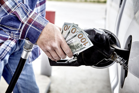 gas nozzle: Mans hand holding forty dollars cash and gas nozzle while  pumping gas into parked vehicle Stock Photo