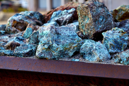 mined: Chunks of copper ore mineral rocks in an iron barrel Stock Photo
