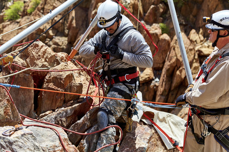 safety harness: Rescue worker setting up his safety harness and ropes under the vortex multipod while sitting on rocks on cliffside